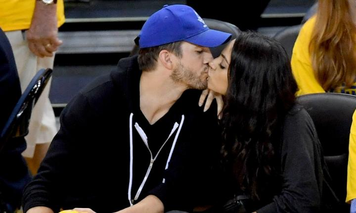 Mila and Ashton share a court-side kiss. Source: Getty