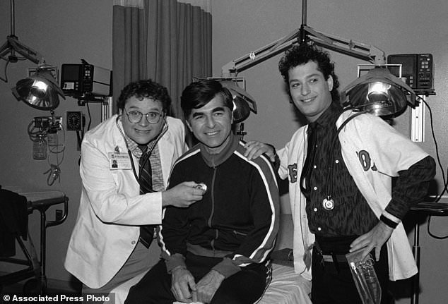 "In this Nov. 9, 1984, file photo, Massachusetts Gov. Michael Dukakis, center, receives treatment from Stephen Furst, left, and Howie Mandel, stars of NBC's television series ""St. Elsewhere,"" in Los Angeles during taping for an episode in which Dukakis played himself and received treatment for a foot injury suffered while jogging. Furst's family says the ""Animal House"" actor has died. Nathan Furst said Saturday, June 17, 2017, that his father died of complications from diabetes. Stephen Furst was 63. He died Friday at his home in Moorpark, Calif., north of Los Angeles. (AP Photo/Robert Gabriel, File)"