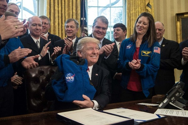 Source: Yahoo (President Donald Trump displays a NASA jacket after signing legislation to send a manned mission to Mars in the 2030s)