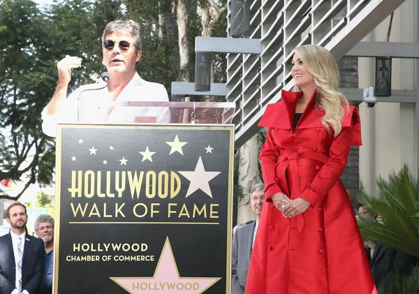 Carrie Underwood stands beside Simon Cowell